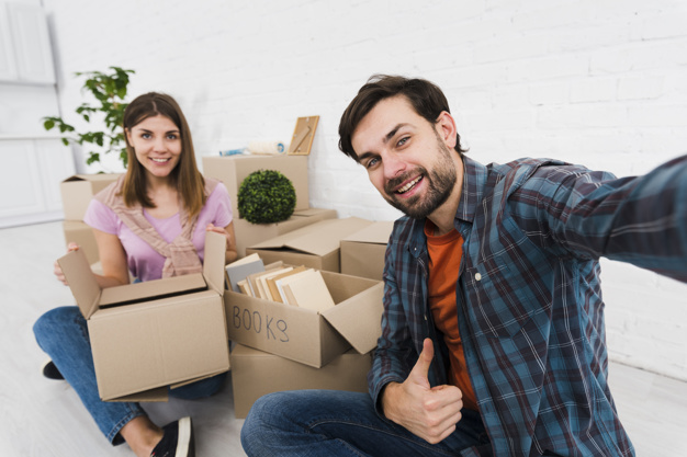 young-couple-moving-together-new-house-unpacking-cardboard-boxes-taking-sulfide_23-2148095510